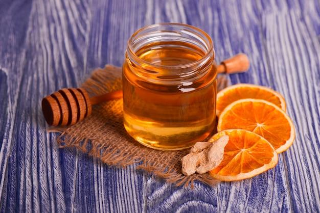Mel em frasco de vidro, gengibre e fatias secas de laranja na mesa de madeira vintage. especiarias aromáticas.