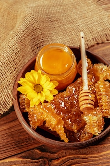 Mel em pote com dipper mel em fundo de madeira vintage