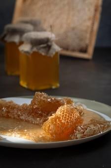 Mel em potes de vidro e favos de mel em cima da mesa.