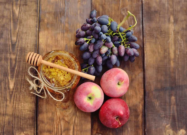 Mel em um frasco bonito, fuso de colher de pau, uvas e maçãs em um fundo de madeira