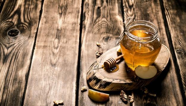 Mel em uma jarra com nozes e fatias de maçã. em fundo de madeira.