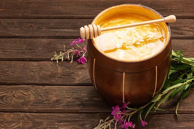 Mel em uma jarra de madeira com uma colher de mel