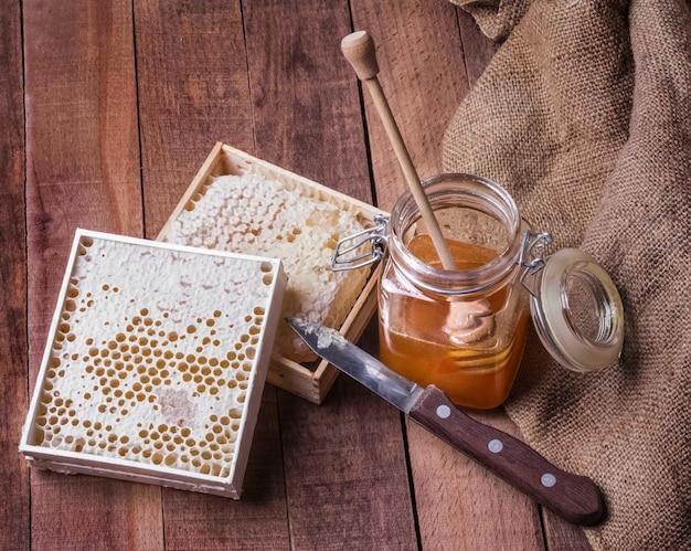 Mel em uma jarra de vidro e favo de mel com uma faca em um fundo de madeira