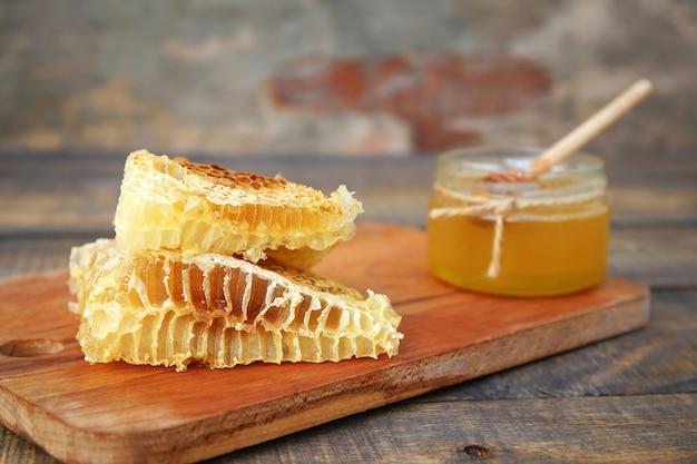 Mel em uma jarra e favo de mel em madeira velha