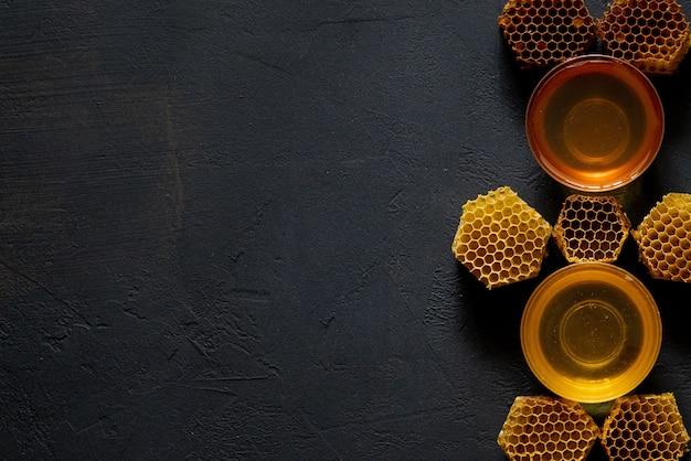 Mel em uma jarra e um favo de mel. sobre um fundo preto de madeira. espaço livre para texto. vista do topo.