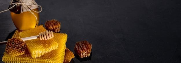 Mel em uma jarra e um favo de mel. sobre um fundo preto de madeira.
