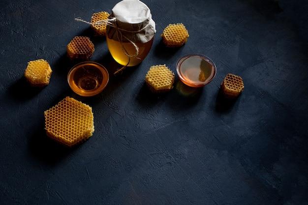 Mel em uma jarra e um favo de mel.