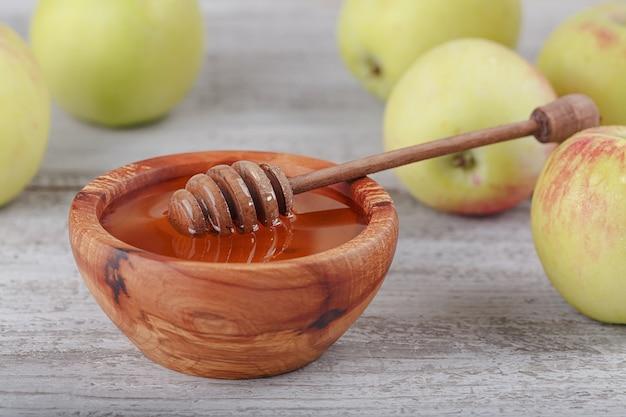 Mel em uma tigela de madeira com concha de mel e maçãs verdes em fundo branco de madeira vintage