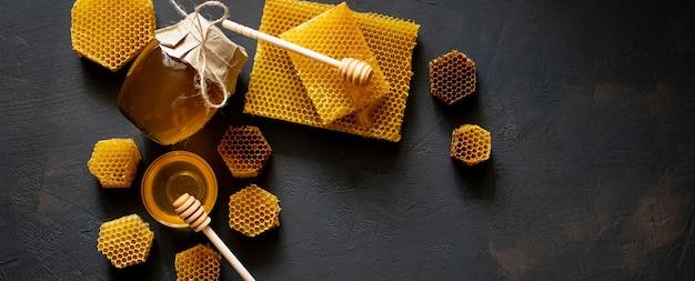 Mel espesso saudável mergulhando da colher de mel de madeira, produtos da abelha pelo conceito de ingredientes naturais orgânicos.