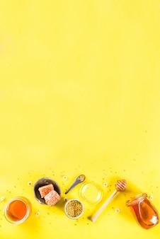 Mel floral orgânico, em frascos, com pentes de pólen e mel, com flores silvestres layout criativo fundo amarelo brilhante vista superior espaço de cópia
