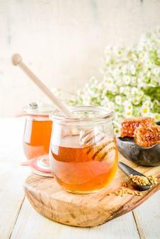 Mel floral orgânico, em frascos, com pentes de pólen e mel, em uma mesa de madeira branca, com flores silvestres