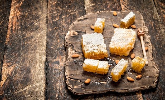 Mel fresco com amêndoas. em fundo de madeira.