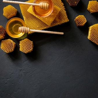 Mel grosso saudável mergulhando da colher de mel de madeira, produtos da abelha pelo conceito de ingredientes naturais orgânicos.