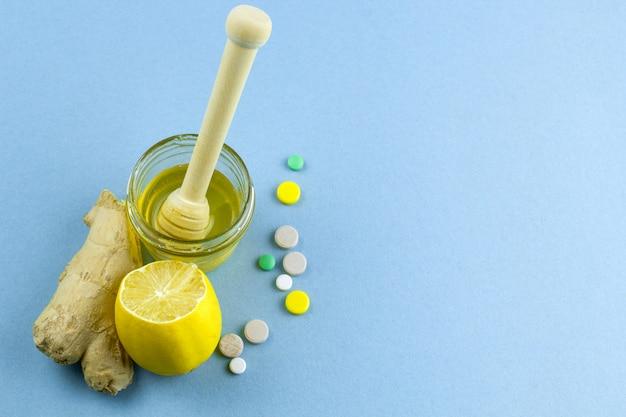 Mel, limão, gengibre e frio pílulas fundo azul, lugar para texto