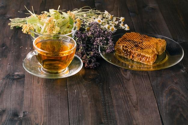 Mel líquido com favo de mel e xícara de chá dentro de monte de ervas secas sobre a superfície de madeira branca
