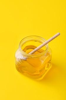 Mel líquido da flor no frasco de vidro com a colher de madeira do mel.