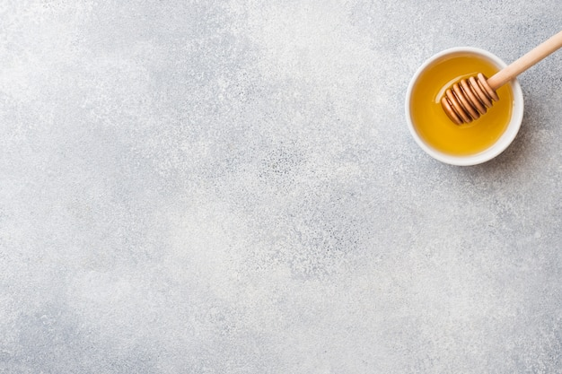 Mel líquido e palito de mel em um