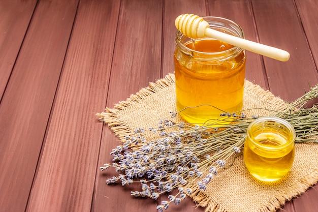 Mel líquido fresco em potes de vidro com uma concha de sopa de mel em madeira