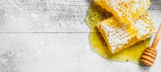 Mel natural em favos de mel com colheres de pau. sobre um fundo rústico.