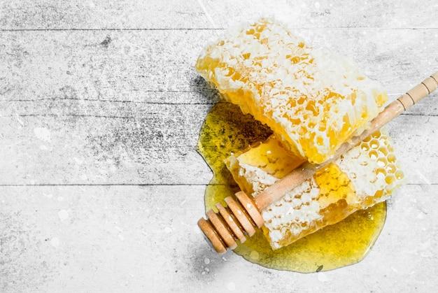 Mel natural em favos de mel com colheres de pau. sobre uma mesa rústica.