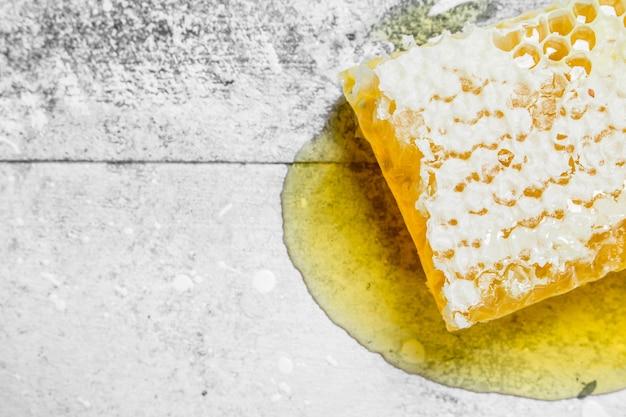 Mel natural em favos de mel. sobre uma mesa rústica.