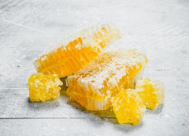 Mel natural em favos de mel. sobre uma superfície rústica.