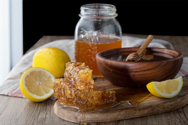 Mel no frasco com favo de mel e drizzler de madeira com limão na mesa de madeira. fundo escuro