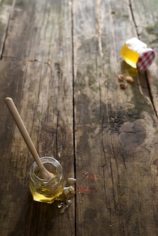 Mel orgânico no frasco com uma vara de madeira em um fundo de madeira velho