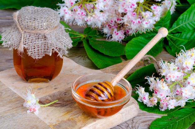 Mel perfumado da castanha no frasco com flores da flor.