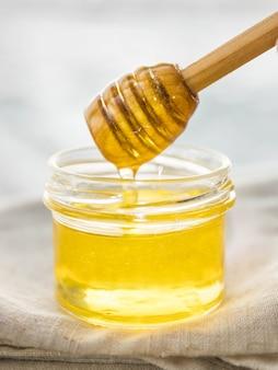 Mel pingando da concha de mel na jarra de vidro