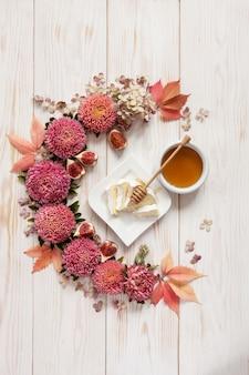 Mel, queijo macio e figos no fundo de madeira branco cercado pelo teste padrão floral de flores e de folhas cor-de-rosa.