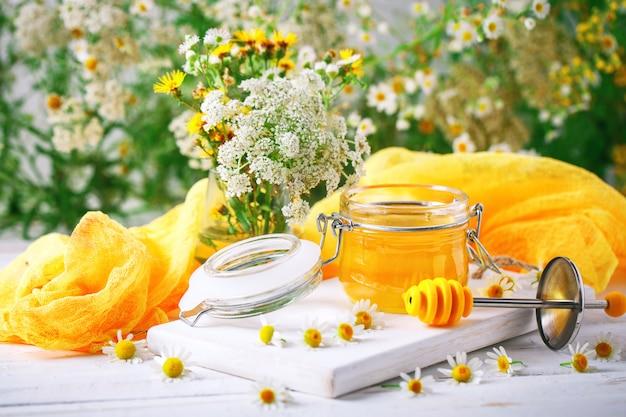 Mel saboroso e saudável na mesa de madeira branca com flores de camomila.