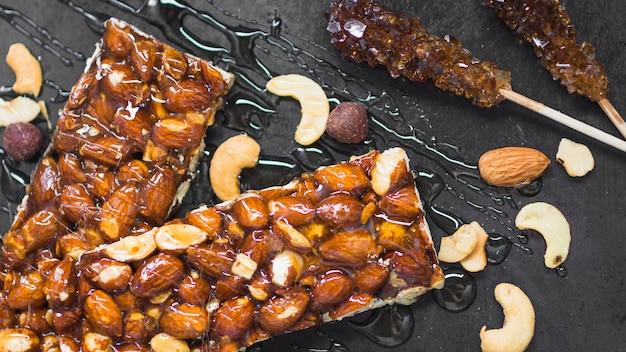 Mel sobre as barras de granola frutas secas no pano de fundo preto