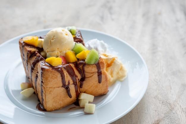 Mel torrada baunilha sorvete com frutas fatiadas e molho de chocolate
