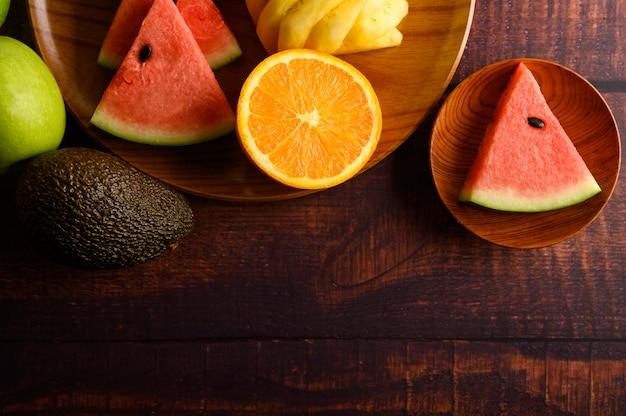 Melancia, abacaxi, laranjas, cortadas em pedaços com abacate e maçãs na mesa de madeira. vista do topo.