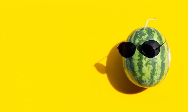 Melancia com óculos escuros sobre fundo amarelo. aproveite o conceito de férias de verão.