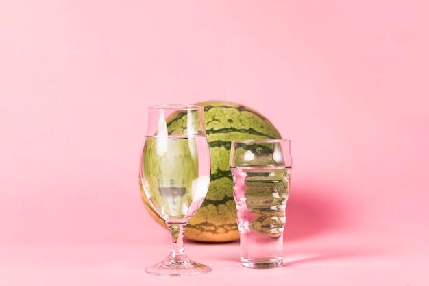 Melancia e copos no fundo rosa