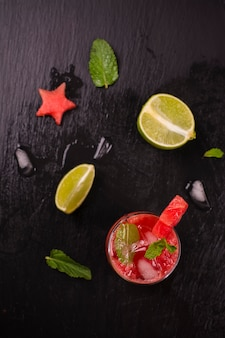 Melancia e limão fresco em copos altos decorados por estrelas de melancia na mesa de pedra preta