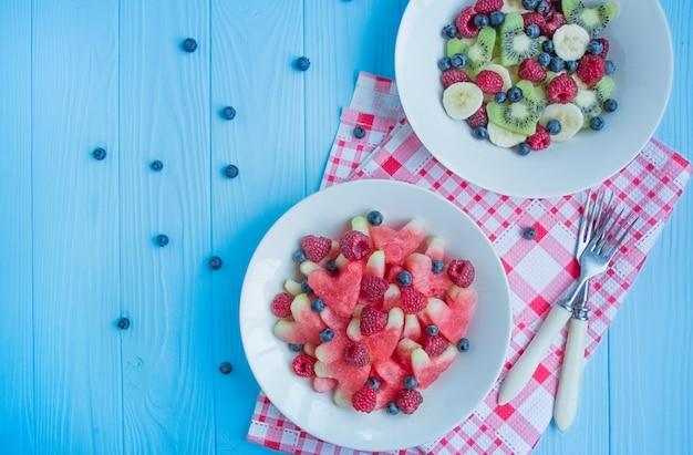 Melancia em forma de corações, framboesas, mirtilos em um prato branco. espaço para texto. lanche de frutas. conceito de amor para dia dos namorados.