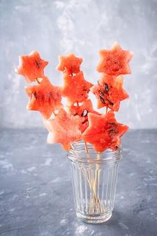 Melancia em forma de estrelas no espeto com folhas de hortelã é em um frasco de vidro.