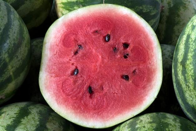 Melancia fatiada sobre a pilha de frutas inteiras
