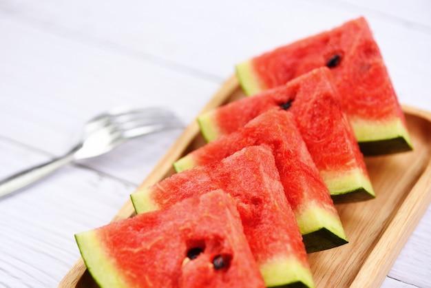 Melancia frutas tropicais na bandeja de madeira - fatia de melancia fresca no fundo branco de madeira