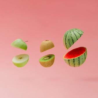 Melancia, maçã e kiwi cortados na parede rosa pastel. conceito mínimo de fruta.