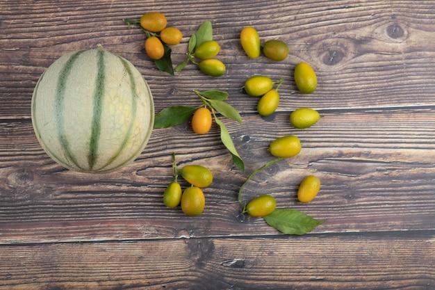 Melão branco e frutas frescas de kumquat na mesa de madeira.