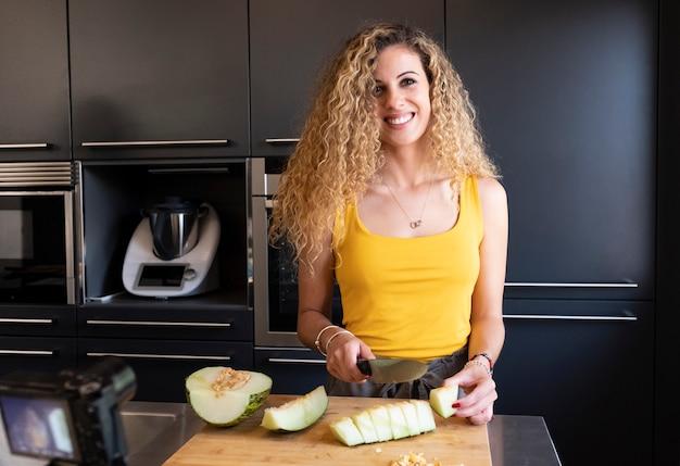 Melão caucasiano da estaca da mulher em uma cozinha.
