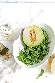 Melão com salada de rúcula em uma tigela