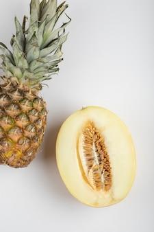 Melão cortado ao meio e abacaxi delicioso maduro na mesa branca.