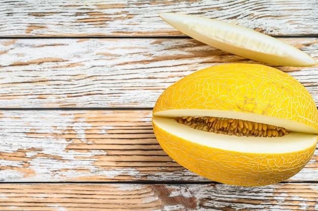 Melão de corte maduro amarelo. fundo de madeira branco. vista do topo. copie o espaço.