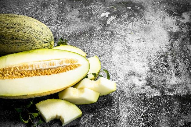 Melão fatiado maduro fresco na mesa rústica.