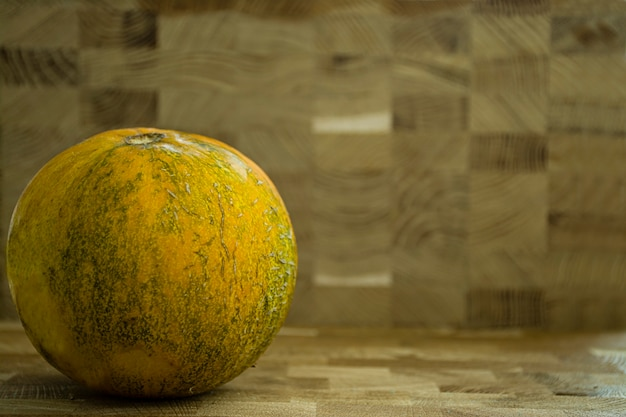 Melão fresco, inteiro em um fundo de madeira.